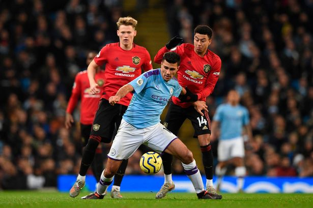 Rodri holds the ball from Jesse Lingard and Scott McTominay